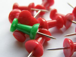 A green pin among red pins